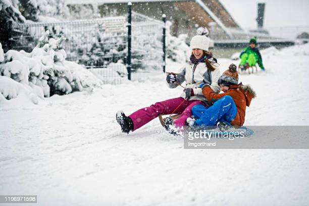 children sledding in winter. - tobogganing stock pictures, royalty-free photos & images