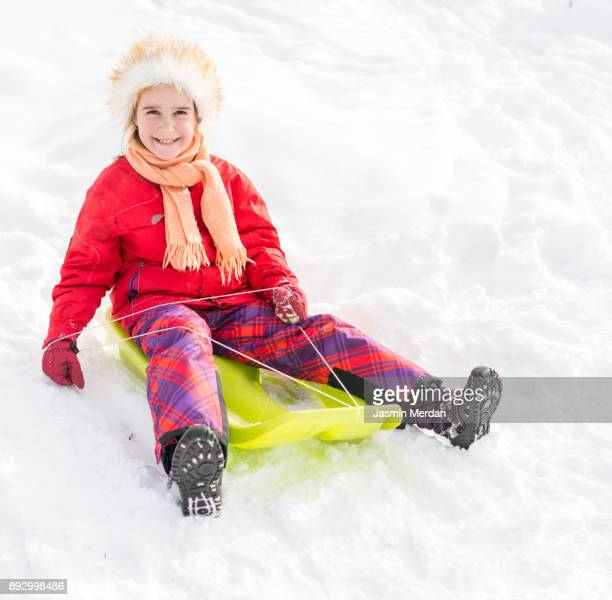 children sledding on snow and having fun - ski wear stock pictures, royalty-free photos & images