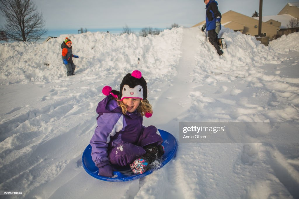 Little girl rides down a little snow hill on a snow sled disk with a big grin on her face and her hair blowing in the wind while a little boy plays in the back ground and a father figure watches.