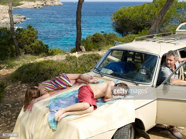 Kinder schlafen auf der Kapuze mit dem Auto