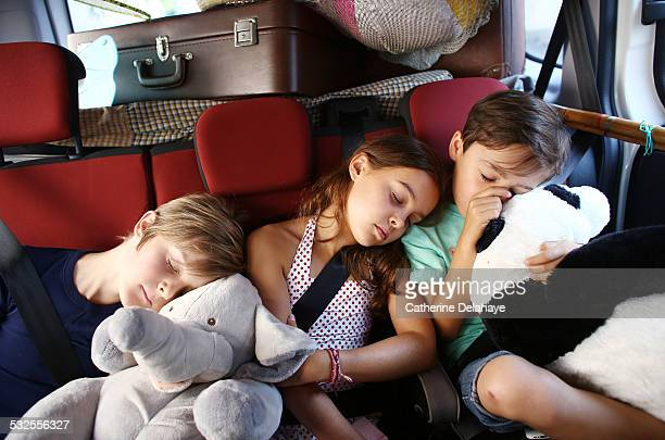 3 children sleeping in a car