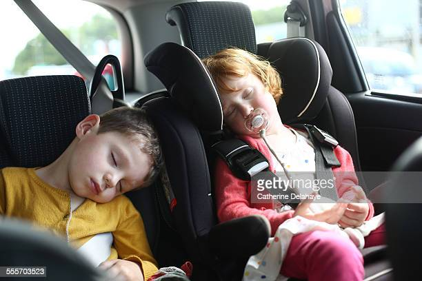 2 children sleeping in a car