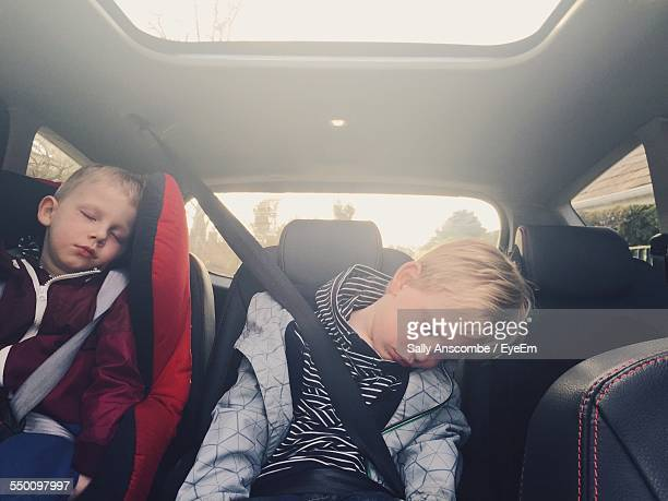 children sleeping in backseat of car - family inside car stock photos and pictures