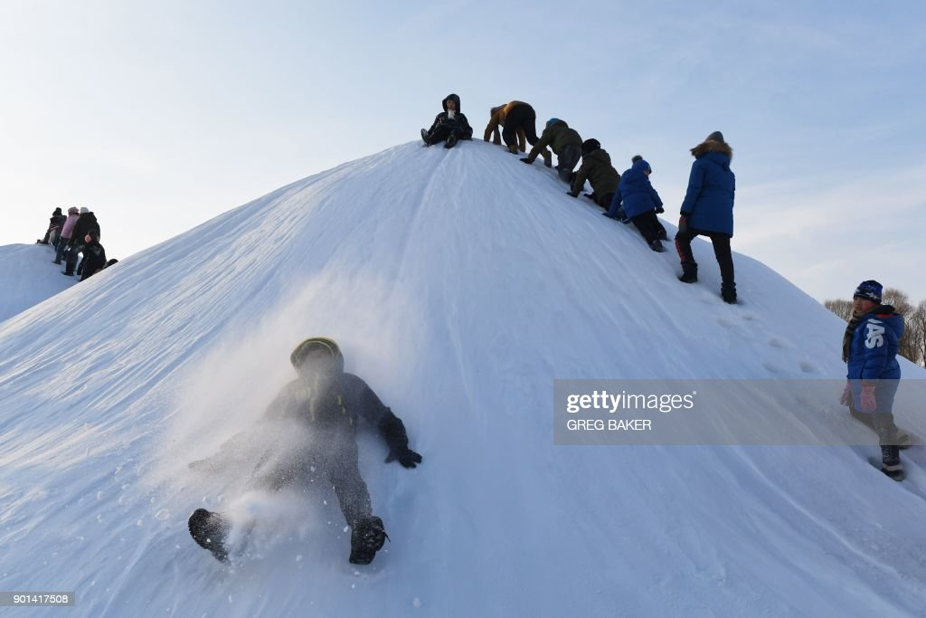 Children slide down a snow hill before the opening of the annual Harbin Ice and Snow Sculpture Festival in Harbin in China's northeast Heilongjiang province on January 5, 2018. The festival attracts hundreds of thousands of visitors annually. / AFP PHOTO / Greg Baker