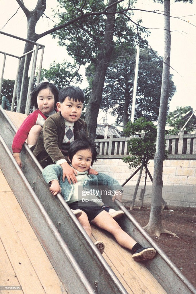 Children sliding down a slide : Stock Photo