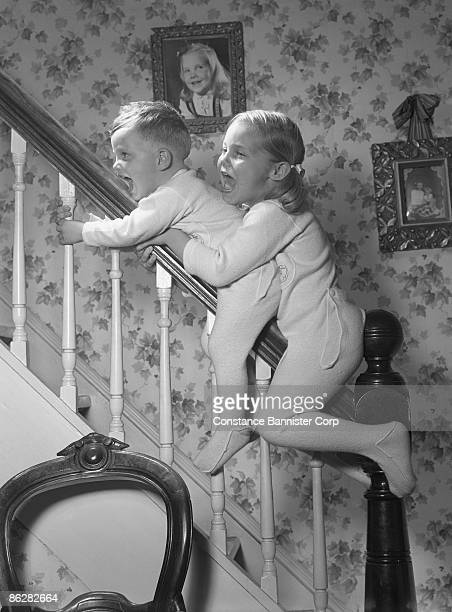 children sliding down banister - constance bannister stock photos and pictures