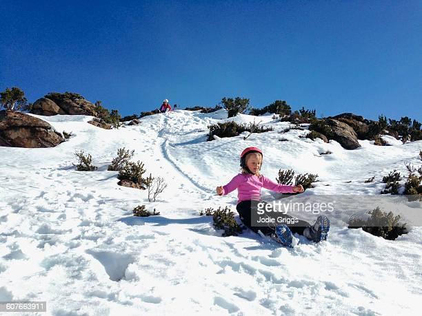 Children sliding down snow covered hill
