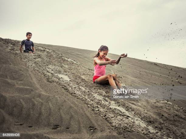 Children sliding on sand dune