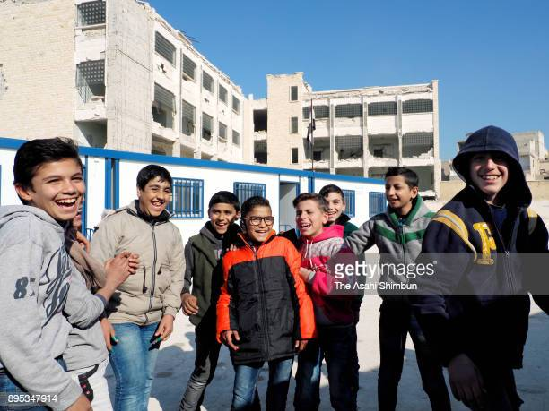 Children smile at their school on December 12 2017 in Aleppo Syria Bashar alAssad administration backed by Russia recaptured the area in December 2016