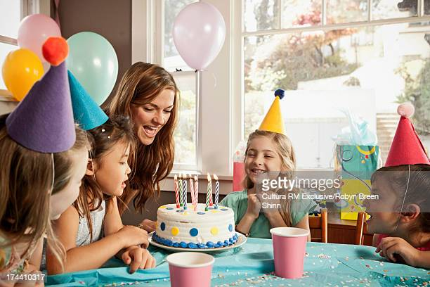 Children smiling and looking at birthday cake
