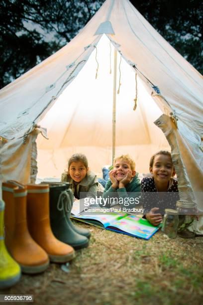 Children smiling in tent at campsite