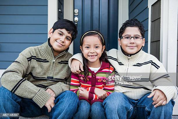 Children smiling together on front stoop