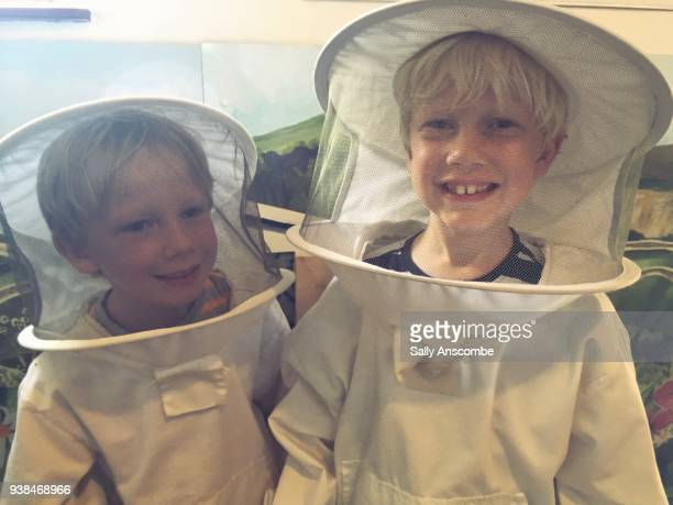 Children smiling wearing beekeeping clothes