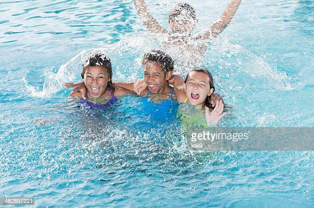 Children splashing in swimming pool.