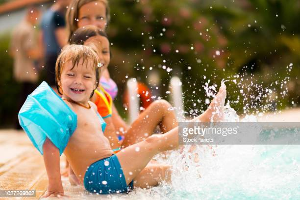 children splashing with water at the pool - girl sitting on boys face stock photos and pictures