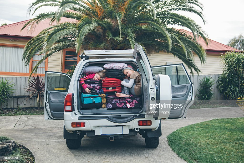 Children squashed into back of car with luggage : Stock Photo