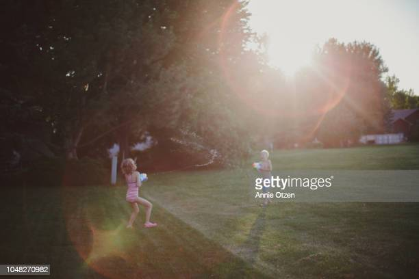 children squirting squirt guns - kids playing tag stock photos and pictures