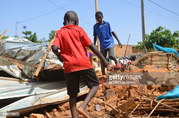 Children stand among debris of a damaged house following heavy rains in Niamey on June 15 2017 At least nine children have been killed in Niger as...