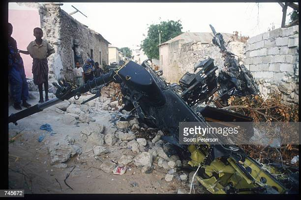 Children stand among the wreckage of an American helicopter October 14, 1993 in Mogadishu, Somalia. This Blackhawk helicopter, which was used to root...