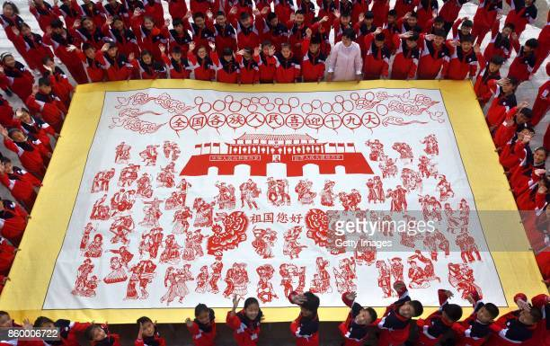 Children stand around their teacher's papercutting work to cheer for the upcoming 19th CPC National Congress on October 10 2017 in Linyi Shandong...