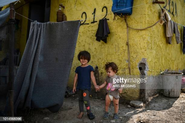 Children stand at a camp next to the Moria refugee camp in the island of Lesbos on August 5 2018