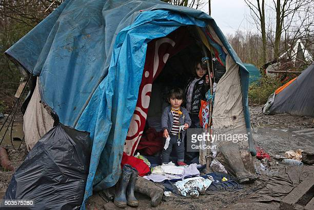 Children stand at the entrance to their shelter in a new migrant camp on January 6 2016 in Dunkirk France Thousands of migrants continue to live in...