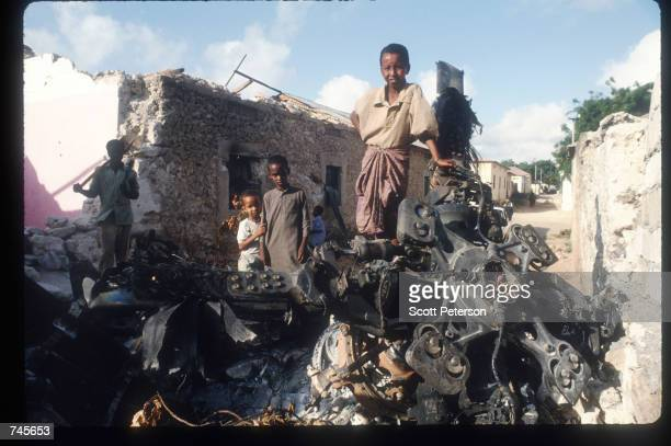 Children stand atop the wreckage of an American helicopter October 14 1993 in Mogadishu Somalia This Blackhawk helicopter which was used to root out...