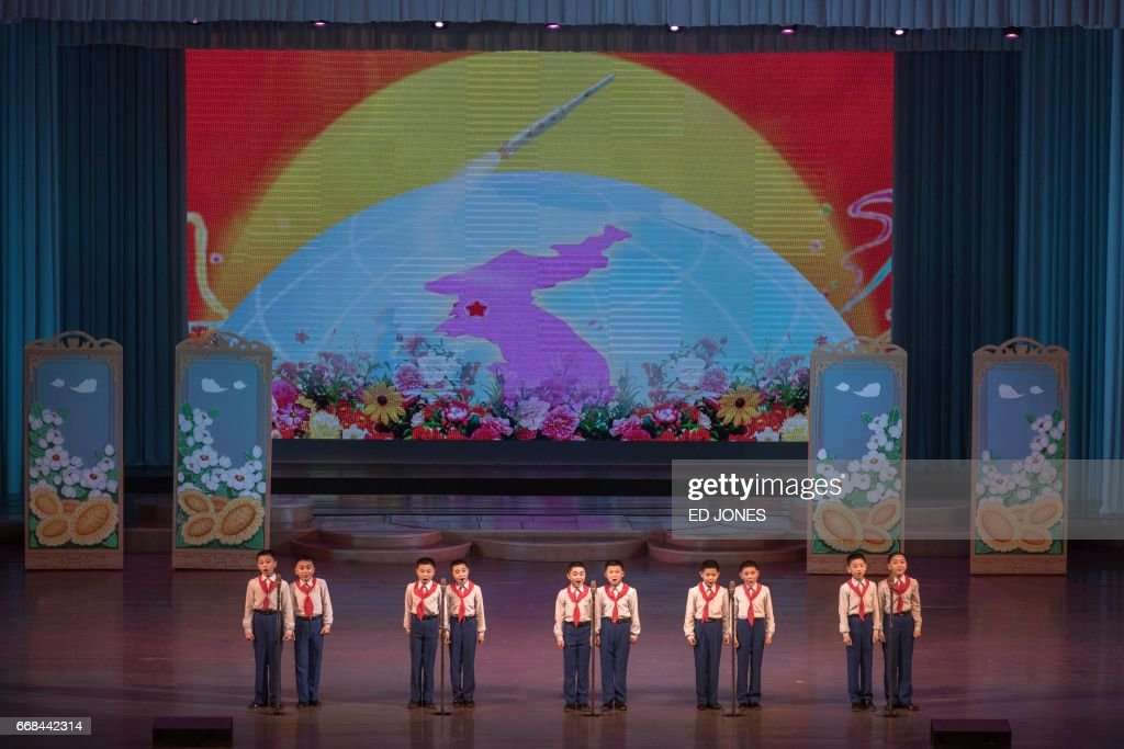 Children stand before an image of a unified Korean peninsula as they perform a variety dance and music show during an organised tour of the Childrens Cultural Palace for visiting foreign journalists on the outskirts of Pyongyang on April 14, 2017. / AFP PHOTO / Ed JONES