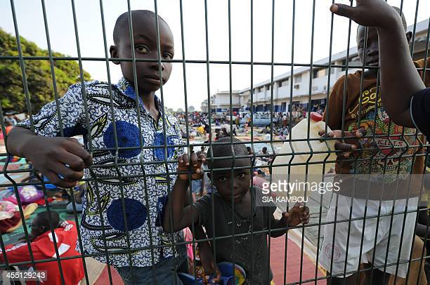 Children stand behind a fence as they wait to receive water in a refugee camp near the airport in Bangui after fleeing violence on December 11 2013...