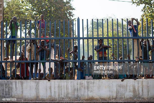 Children stand behind the fence of the French military base camp part of the Operation Sangaris in Bossangoa on December 18 2013 The Central African...