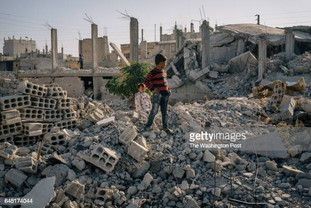 Children stand by buildings destroyed in a US airstrike that targetted ISIS militants but also killed nine members of the same famiy in Manbij