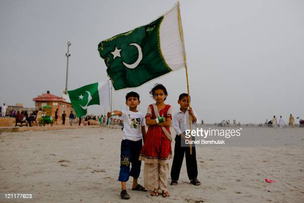 Children stand for a portrait taken by their father as people gather at Seaview waterfront to celebrate Pakistan's Independence Day on August 14 2011...