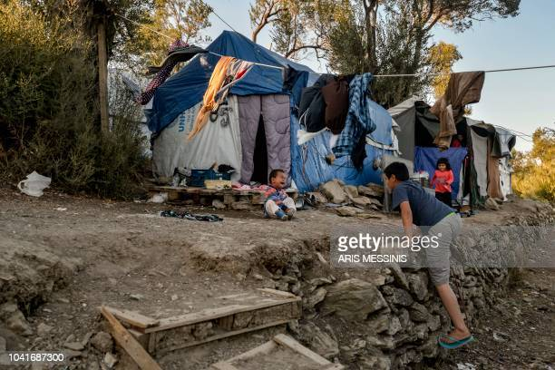 Children stand in a camp outside the refugee camp of Moria in the northern Greek island of Lesbos on September 25 2018 Despite a 2016 agreement...