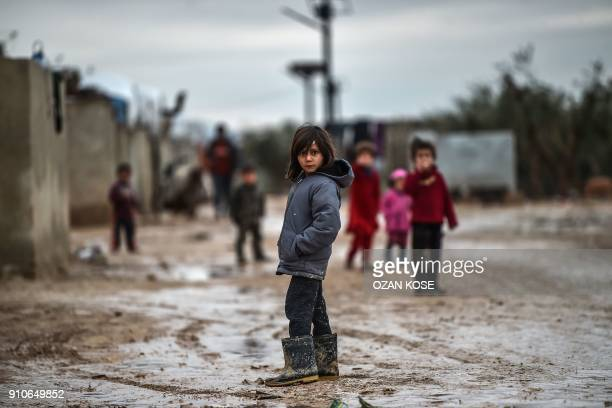 Children stand in a muddy street at a refugee camp on January 26 2018 at the Syrian town of Azaz The Turkish military on January 20 launched...