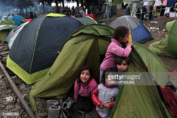 Children stand in a tent on March 10 2016 at the GreekMacedonian border near the Greek village of Idomeni where thousands of refugees and migrants...