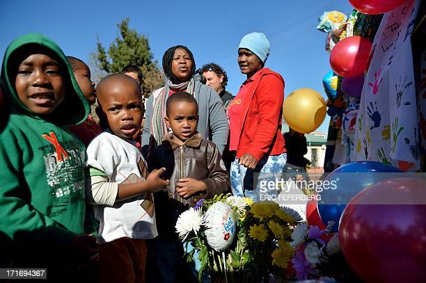 Children stand in front of messages left for Nelson Mandela oustide the Mediclinic Hear hospital on June 28, 2013 in Pretoria. A gravely ill Nelson...