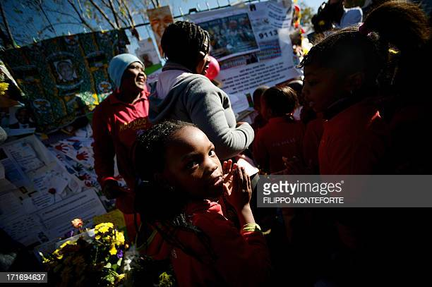 Children stand in front of messages left for Nelson Mandela outside the Medi Clinic Heart hospital in Pretoria on June 28, 2013. A gravely ill Nelson...