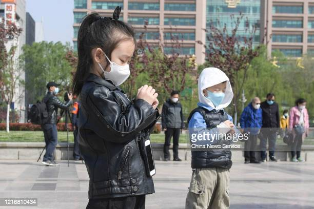 Children stand in silent tribute at a square during a three minute national memorial to mourn martyrs who died in the fight against the novel...