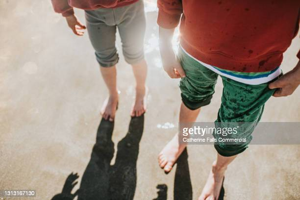 children stand in the sea and let the tide roll over their little feet - low tide stock pictures, royalty-free photos & images