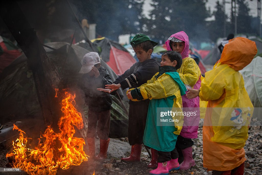 Children stand near a burning tyre that has been lit at the Idomeni refugee camp on March 13, 2016 in Idomeni, Greece. The decision by Macedonia to close its border to migrants on Wednesday has left thousands of people stranded at the Greek transit camp. The closure, following the lead taken by neighbouring countries, has effectively sealed the so-called western Balkan route, the main migration route that has been used by hundreds of thousands of migrants to reach countries in western Europe such as Germany. Humanitarian workers have described the conditions at the camp as desperate, which has been made much worse by recent bouts of heavy rain.