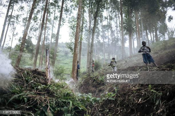 Children stand near a charcoal production furnace as part of the WWF Ecomakala project to reduce illegal charcoal production, in Burungu,...
