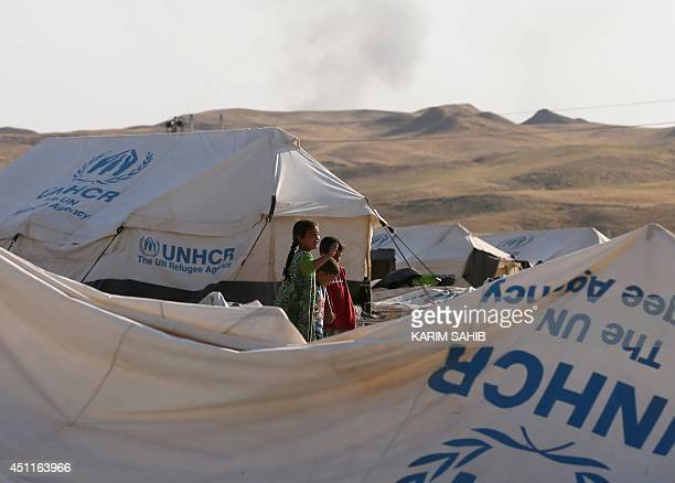 Children stand near tents at a camp for displaced Iraqi Shiite Turkmen who fled their town of Tal Afar, in Shikhan, in Kurdistan's Dohuk province, on...