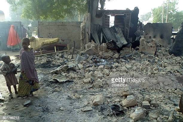 Children stand near the rubble of a burnt house after Boko Haram attacks at Dalori village on the outskirts of Maiduguri in northeastern Nigeria on...
