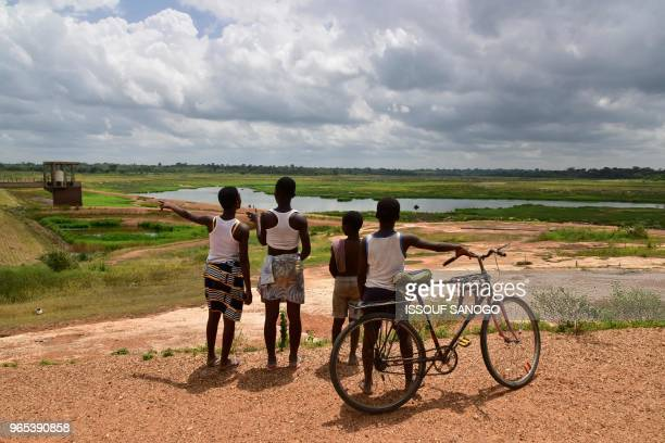 Children stand next to Asseche Dam of the Company of Distribution of water of Ivory Coast in Angoua-Yaokro near Bouaké, on June 1, 2018. - The...