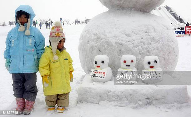 Children stand next to snowmen during the 60th Sapporo Snow Festival on February 5 2009 in Sapporo Japan The 60th Sapporo Snow Festival takes place...