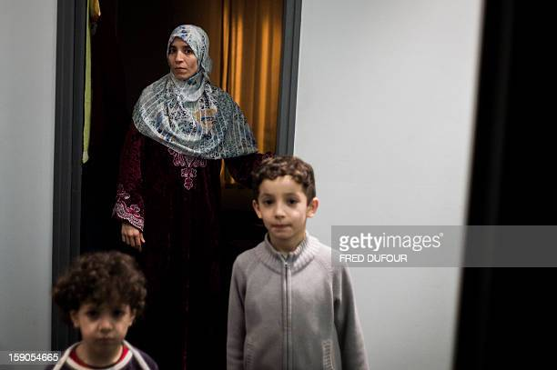 Children stand next to their mother in a corridor in front of the room they occupied in a building requisitioned by French associations 'Jeudi Noir'...