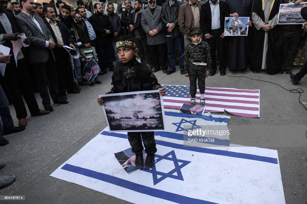 Children stand on an Israeli and a US flag as Palestinian supporters of the Islamic Jihad movement take part in a protest against the US president's decision to recognise Jerusalem as the capital of Israel, in the town of Rafah in the southern Gaza Strip, on January 12, 2018. /