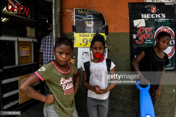 Children stand outside a convenience store located in a low income mostly AfricanAmerican neighbourhood in Miami on April 17 2020