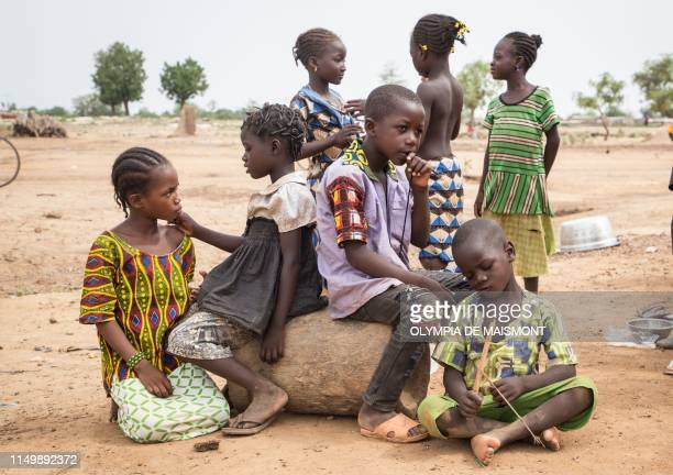Children stand outside a school used as a shelter for Internally Displaced People from northern Burkina Faso on June 13, 2019 in Ouagadougou. -...