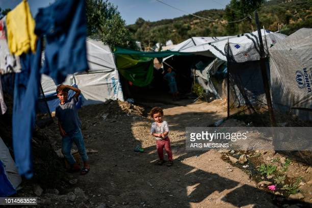 Children stand outside tents at a camp next to the Moria refugee camp in the island of Lesbos on August 05 2018